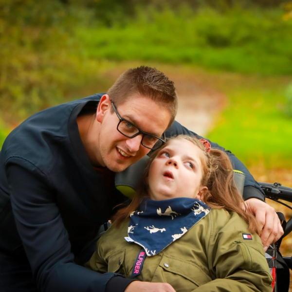 vader met kind in rolstoel